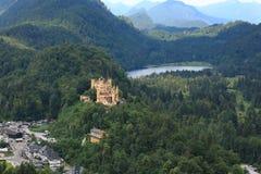 Οι γραφικοί λόφοι των Άλπεων, η λίμνη που περιβάλλεται με τους χαμηλούς βράχους που εισβάλλονται με το πυκνό ξύλο είναι ορατοί το στοκ φωτογραφία με δικαίωμα ελεύθερης χρήσης
