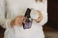 Οι γυναίκες δίνουν τον καθαρίζοντας μαύρο φακό γυαλιών ηλίου με το καφετί backgr θαμπάδων Στοκ φωτογραφίες με δικαίωμα ελεύθερης χρήσης