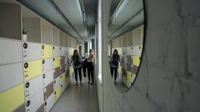 Οι γυναίκες εισάγουν το διάδρομο γραφείων με το παράθυρο ενδυμάτων απόθεμα βίντεο