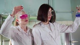 Οι γυναίκες εξετάζουν τη χημική αντίδραση στο ιατρικό εργαστήριο φιλμ μικρού μήκους