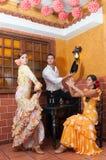 Οι γυναίκες και ο άνδρας στα παραδοσιακά flamenco φορέματα χορεύουν κατά τη διάρκεια Feria de Abril τον Απρίλιο Ισπανία στοκ εικόνες