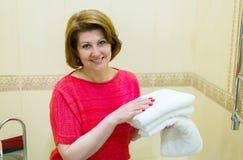 Οι γυναίκες κρατούν τις καθαρές άσπρες πετσέτες στο λουτρό Στοκ φωτογραφία με δικαίωμα ελεύθερης χρήσης