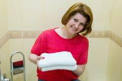 Οι γυναίκες κρατούν τις καθαρές άσπρες πετσέτες στο λουτρό Στοκ εικόνα με δικαίωμα ελεύθερης χρήσης