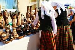 Οι γυναίκες με τα εθνικά κοστούμια αγοράζουν τα χειροποίητα δοχεία αργίλου Στοκ φωτογραφία με δικαίωμα ελεύθερης χρήσης