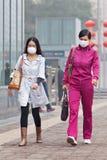 Οι γυναίκες με την προστασία αναπνοής σε μια αιθαλομίχλη καλθηκαν την πόλη, Πεκίνο, Κίνα Στοκ Φωτογραφίες