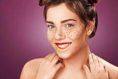 Οι γυναίκες νεολαίας με ακτινοβολούν φακίδες στο πρόσωπο, ρόδινο υπόβαθρο τέλειο δέρμα τέχνης ανασκόπησης μαύρο έννοιας μασκών λε Στοκ Φωτογραφία