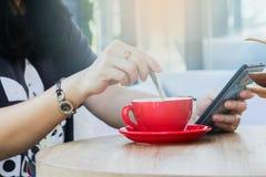 Οι γυναίκες παίζουν τα έξυπνα τηλέφωνα στις καφετερίες στοκ φωτογραφίες με δικαίωμα ελεύθερης χρήσης