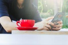 Οι γυναίκες παίζουν τα έξυπνα τηλέφωνα στις καφετερίες στοκ εικόνες