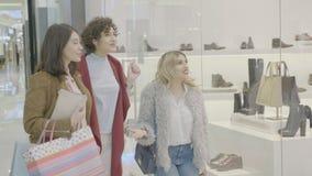 Οι γυναίκες που εξετάζουν το τέλειο ζευγάρι των παπουτσιών στο παράθυρο αποθηκεύουν και που εκφράζουν τη χαρά τους κρατώντας τις  απόθεμα βίντεο
