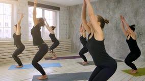 Οι γυναίκες που κάνουν το χαιρετισμό ήλιων γιόγκας θέτουν στο εσωτερικό στο στούντιο γιόγκας Στοκ Εικόνες