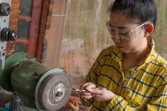 Οι γυναίκες που στέκονται είναι ακονίζουν το τρυπάνι σε έναν πάγκο εργασίας με τη μηχανή ακονών στοκ φωτογραφία