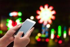 Οι γυναίκες που χρησιμοποιούν το έξυπνο τηλέφωνο στη θολωμένη ελαφριά οδό Στοκ φωτογραφία με δικαίωμα ελεύθερης χρήσης
