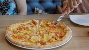 Οι γυναίκες σε έναν καφέ σχεδιάζουν τις φέτες της πίτσας στα πιάτα φιλμ μικρού μήκους