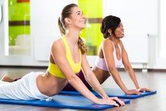 Οι γυναίκες στη γυμναστική που κάνει τη γιόγκα ασκούν για την ικανότητα στοκ φωτογραφία