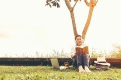 Οι γυναίκες τρόπου ζωής απολαμβάνουν τη μουσική ακούσματος και ανάγνωση ενός βιβλίου και παίζουν το lap-top στον τομέα χλόης του  στοκ εικόνα