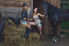 Οι γυναίκες φλερτάρουν στο αγρόκτημα, οι στάσεις αλόγων εδώ κοντά Στοκ Φωτογραφία