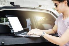 Οι γυναίκες χρησιμοποιούν το lap-top ως επιχειρησιακές επαφές Στην περιοχή αυτοκινήτων της ` s στοκ εικόνα
