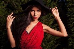 Οι γυναίκες brunette ομορφιάς στο κόκκινα φόρεμα & το καπέλο θέτουν τη νύχτα το πάρκο Στοκ Φωτογραφία
