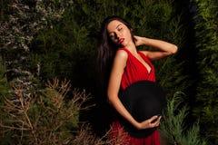 Οι γυναίκες brunette ομορφιάς στο κόκκινα φόρεμα & το καπέλο θέτουν τη νύχτα το πάρκο Στοκ φωτογραφίες με δικαίωμα ελεύθερης χρήσης
