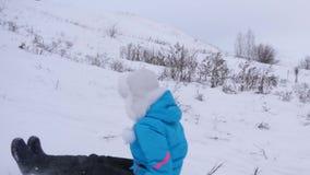 Οι γύροι κοριτσιών από το υψηλό βουνό στο πιατάκι χιονιού πέρα από το χιόνι το χειμώνα και γελούν με την ευχαρίστηση Εύθυμο γυναι απόθεμα βίντεο