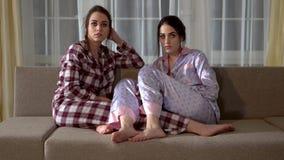 Οι δίδυμες αδελφές στις πυτζάμες κάθονται στον καναπέ και επιλέγουν τι να προσέξει στη TV στο καθιστικό σχέση απόθεμα βίντεο