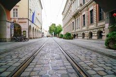 Οι διαδρομές σιδηροδρόμων που οργανώνονται μέσω της οδού κυβόλινθων μεταξύ της πόλης χτίζουν Στοκ Φωτογραφίες