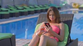 Οι διακοπές θερέτρου, όμορφο νέο κορίτσι στο κοστούμι λουσίματος που στηρίζεται κοντά στην μπλε λίμνη στον αργόσχολο ήλιων εξετάζ απόθεμα βίντεο