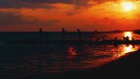 Οι διακοπές θερινών παραλιών στο ηλιοβασίλεμα, παιδιά που τρέχει γύρω από τη χορεύοντας γέφυρα, παιχνίδι προφθάνουν στο ηλιοβασίλ απόθεμα βίντεο
