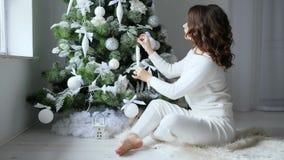 Οι διακοπές πρωί, κορίτσι με την καφετιά τρίχα διακοσμούν το εορταστικό χριστουγεννιάτικο δέντρο στους μαλακούς άσπρους τόνους απόθεμα βίντεο