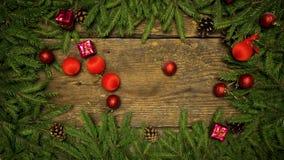 Οι διακοσμήσεις Χριστουγέννων που αφορούν ένα ξύλινο υπόβαθρο με το έλατο διακλαδίζονται και κώνοι έτοιμοι για το σχέδιό σας οι δ απόθεμα βίντεο