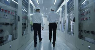 Οι διαφορετικοί συνάδελφοι που περπατούν στο σταθμό παραγωγής ηλεκτρικού ρεύματος στρέφονται απόθεμα βίντεο