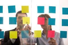 Οι διαφορετικοί συνάδελφοι συζητούν τις ιδέες κοινές στις κολλώδεις σημειώσεις στοκ εικόνα