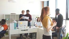 Οι διεθνείς ανεξάρτητοι εργαζόμενοι μιλούν μαζί στις μικρές υποομάδες στο δωμάτιο με το ύφος σοφιτών φιλμ μικρού μήκους
