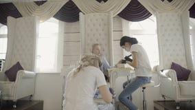 Οι δύο θηλυκοί κύριοι κάνουν το μανικιούρ και το pedicure για τη νέα γυναίκα στο σαλόνι πολυτέλειας φιλμ μικρού μήκους