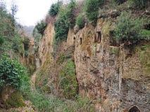 Οι είσοδοι τάφων στον τοίχο του α μέσω της κοίλης φλέβας, ένας αρχαίος δρόμος Etruscan χάρασαν μέσω των απότομων βράχων tufo στην στοκ φωτογραφία με δικαίωμα ελεύθερης χρήσης