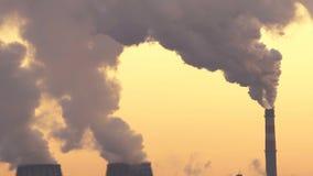 Οι εγκαταστάσεις εκπέμπουν τον καπνό και η αιθαλομίχλη από τους σωλήνες στο ηλιοβασίλεμα, ρύποι εισάγει την ατμόσφαιρα φιλμ μικρού μήκους