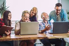 Οι εθελοντές βοηθούν τους ανώτερους ανθρώπους στον υπολογιστή στοκ φωτογραφία