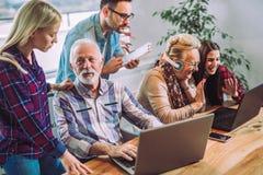 Οι εθελοντές βοηθούν τους ανώτερους ανθρώπους στον υπολογιστή στοκ εικόνα