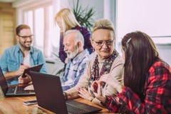 Οι εθελοντές βοηθούν τους ανώτερους ανθρώπους στον υπολογιστή στοκ φωτογραφία με δικαίωμα ελεύθερης χρήσης