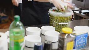Οι ελιές τίθενται στα άσπρα κύπελλα στην κουζίνα απόθεμα βίντεο