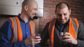 Οι ελκυστικοί οικοδόμοι πίνουν τον καφέ σε ένα σπάσιμο Μιλούν και χαμογελούν απόθεμα βίντεο