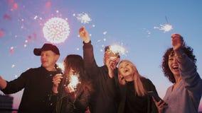 Οι ελκυστικοί, συγκινημένοι νέοι στη στέγη στο χρόνο πυροτεχνημάτων κρατούν τους φωτεινούς φανούς σπινθηρίσματος Δροσερό κόμμα στ απόθεμα βίντεο