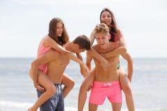 Οι ελκυστικοί χαμογελώντας συνεργάτες κρατούν τα όμορφα κορίτσια σε μια ακτή σε ένα φυσικό θολωμένο υπόβαθρο Στοκ φωτογραφία με δικαίωμα ελεύθερης χρήσης