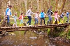 Οι ενήλικοι με τα παιδιά στη γέφυρα στην υπαίθρια δραστηριότητα στρέφονται στοκ εικόνες