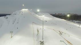 Οι εναέριοι σκιέρ και τα snowboarders ανεβαίνουν τον ανελκυστήρα στην κλίση απόθεμα βίντεο