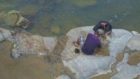 Οι εναέριοι ψαράδες άποψης αφήνουν έξω τα ψάρια να βάλουν στη συνεδρίαση τσαντών στους βράχους απόθεμα βίντεο