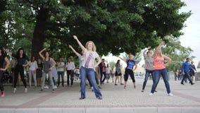 Οι ενεργές γελώντας γυναίκες χορών στους τετραγωνικούς, ευτυχείς ανθρώπους που χορεύουν στην οδό, χορογράφος παρουσιάζουν κινήσει απόθεμα βίντεο