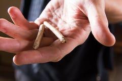 Οι ενώσεις μαριχουάνα επανδρώνουν το χέρι Άτομο που προσφέρει τα φάρμακα Στοκ Εικόνα