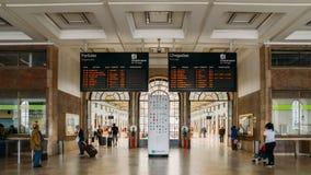 Οι επιβάτες εξετάζουν την ψηφιακή επίδειξη χρονοδιαγράμματος μέσα στο σταθμό τρένου της Λισσαβώνας ` s Santa Apolonia που συνδέει Στοκ φωτογραφίες με δικαίωμα ελεύθερης χρήσης