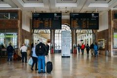 Οι επιβάτες εξετάζουν την ψηφιακή επίδειξη χρονοδιαγράμματος μέσα στο σταθμό τρένου της Λισσαβώνας ` s Santa Apolonia που συνδέει Στοκ Εικόνες